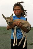 Girl with orphaned gazelle, Gobi Desert, Mongolia, Asia