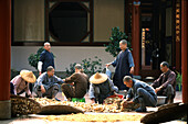 Monks and nuns with harvest at the inner courtyard of a monastery, Tainan, Taiwan, Asia