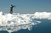 Hunter with rifle standing on the waterfront , Ilulissat, Greenland