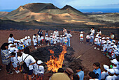 School class gathering around a fire, Timanfaya National Park, Lanzarote, Canary Islands, Spain, Europe