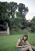 Woman sitting on Loan and writing, Isarauen, Munich, Bavaria, Germany