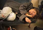 Woman sleeping on a bench, people