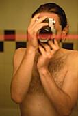 Man photographing himself in mirror, bathroom
