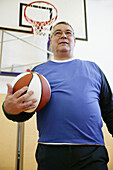 Mature man playing basketball