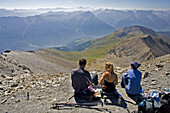 Group of people resting and enjoying the view on the top of the Muttler, Grisons, Switzerland