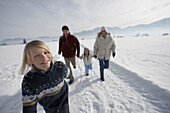 Family with two children walking on snow
