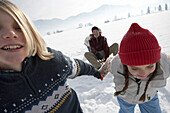 Children pulling parents in toboggan on snow, side view