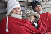 Parents and son leaning on wooden hut, warming with red blanket