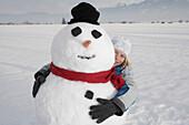Boy hugging a snowman