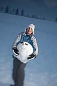 Boy bearing head of snowman