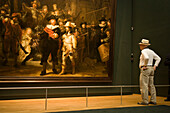 Visitor, Rembrandt, The Nightwatch, Rijksmuseum, Man looking at The Nightwatch, a painting by Rembrandt van Rijn, Rijksmuseum, Amsterdam, Holland, Netherlands