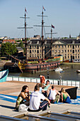 People, Sailing Boat, Terrace Cafe, People on Terrace Cafe of NEMO Center looking to Nederlands Scheepvaartmuseum with replica sailer Amsterdam, Amsterdam, Holland, Netherlands