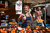 Woman, Monday Flea Market, Noorderkerkplein, Jordaan, Woman talking orange up at Monday flea market Noordermarkt, , Noorderkerkplein, Jordaan, Amsterdam, Holland, Netherlands