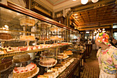 Woman see into outlay full with fancy cakes, Cafe Demel, Vienna, Austria