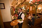 Waiter serving giant Wiener Schnitzel at Restaurant Figlmueller, Vienna, Austria