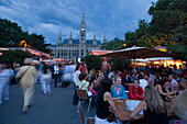 Guests in a pavement cafe near city hall in the evening, Vienna, Austria