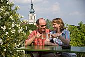 Couple toasting glasses at Heuriger Zawodsky, Grinzing, Vienna, Austria