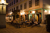 People sitting in the open-air area of the different restaurants in the Bermuda Triangle in the near of Ruprechtskirche in the evening, Vienna, Austria