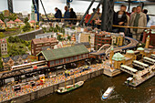 Visitors watching the model railroad, Visitors watching the largest model railroad in the world, the Miniatur Wunderland, Speicherstadt, Hamburg, Germany
