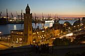 View over Landungsbruecken to dockyard at night, St. Pauli, Hamburg, Germany