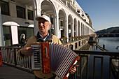 Man playing accordion near the Alsterarkaden, Man playing accordion in the near of the Alsterarkaden on a bridge over the Alsterfleet, Hamburg, Germany