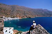 Woman sitting on rock above bay, Loutro, Crete, Greece