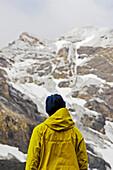 Young female alpinist looking up to mountain, Piz Quattervals, Valetta, Swiss Nationalpark, Engadin, Graubuenden, Grisons, Switzerland, Alps