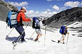 Three alpinists moving down a mountain on snow, Val Sassa, Swiss Nationalpark, Engadin, Graubuenden, Grisons, Switzerland, Alps
