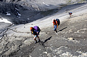 Group of hikers on a remote path in the mountains, Val Mueschauns, Fuorcla Val Sassa, Swiss Nationalpark, Engadin, Graubuenden, Grisons, Switzerland, Alps