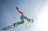 Young woman jumping with snowshoes