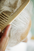 Combing white-haired head