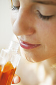 Young woman smelling a bottle of perfumed body oil