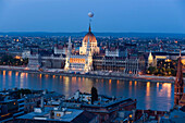 View over the Danube river to the illuminated Parliament in the evening, Pest, Budapest, Hungary