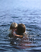 Mother holding little daughter, swimming