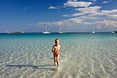 Child running in water, Costa Rei, Sardinia, Italy