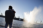 Father holding baby, looking from quay, river Elbe, harbor and docks, St. Pauli, Hamburg, Germany