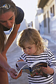 Mother and little daughter looking in guidebook, Karpathos, Dodecanese Islands, Greece