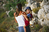 Mother carrying little daughter, Karpathos, Dodecanese Islands, Greece