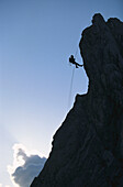 Silhouette of man climbing rock face, side view, Alpspitze, Bavaria, Germany