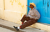 Blind old man sitting in front of a blue gate having a cigar, Havana, Kuba