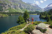 Two hiking women taking a rest in front of a mountain lake, Laegh Cavloc, Cavloc Lake, Forno, Bergell, Graubuenden, Grisons, Switzerland