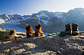 Hiking boots, socks and mountain view. Forno hut, SAC, Bergell, Bregaglia, Graubuenden, Grisons, Switzerland, Alps.
