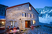 Evening in front of a mountain hut, Forno hut, SAC, Swiss Alpine Club, Bergell, Bregaglia, Graubuenden, Grisons, Switzerland, Alps