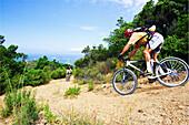Mountainbiker races down to Corsicas westcoast, Corsica, Mediterranean, France