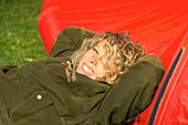 Young woman with a blond curly hair lying in the sun and smiling