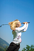 Young woman with blond hair hitting golf ball