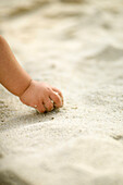 Child's hand playing with sand
