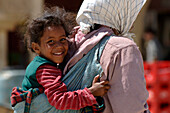 Girl carried by mother, Place el Hedim, Meknes, Morocco