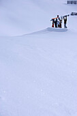Five young people people holding snowboards and skis over heads, Kuehtai, Tyrol, Austria