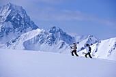 Two skier walking through snow, mountains in the background, Kuehtai, Tyrol, Austria